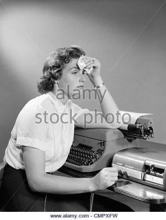 1950s-ailing-woman-secretary-sitting-at-desk-with-typewriter-and-dictation-cmpxfw